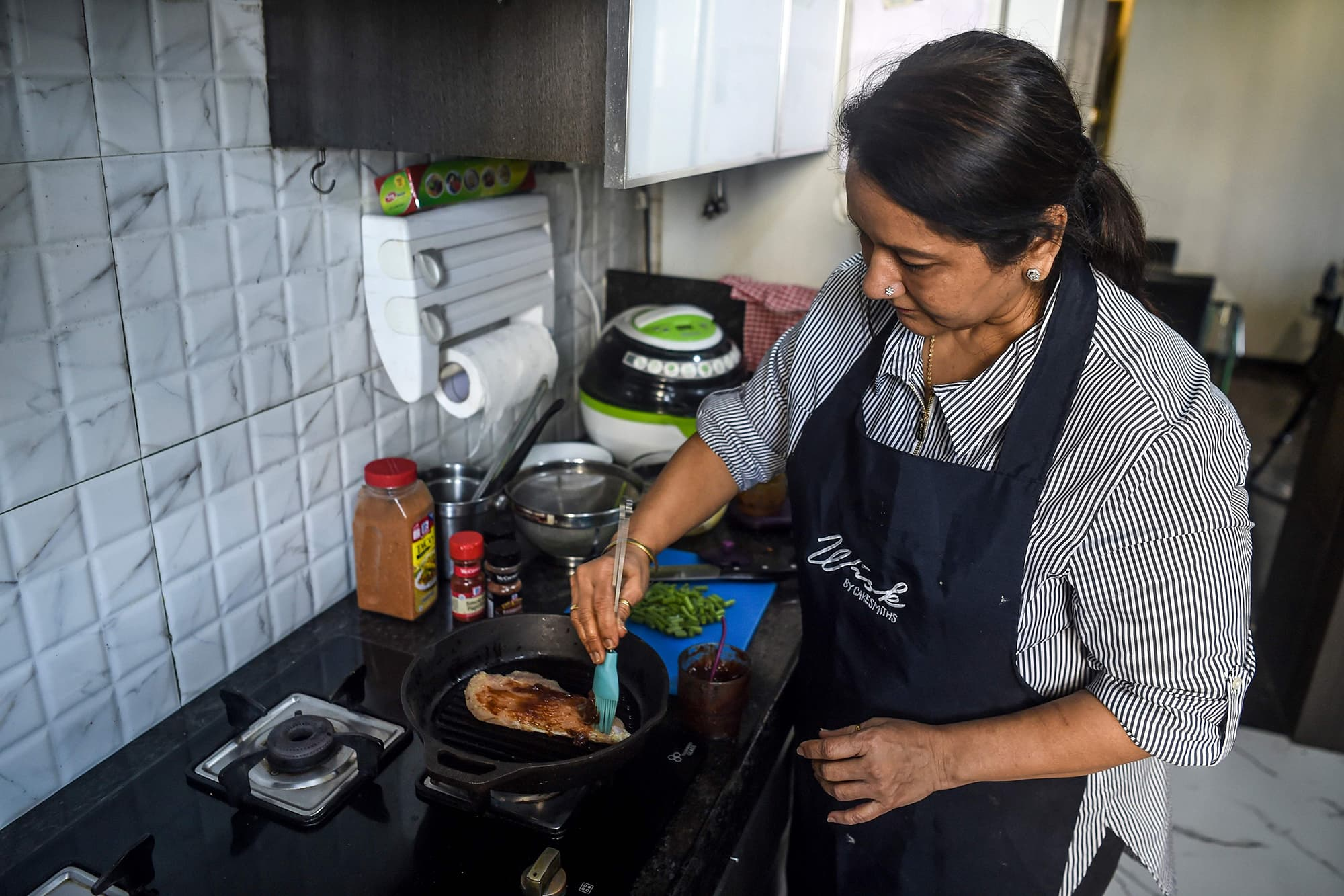 "In this photo taken on January 8, 2020, home chef Rashmi Sahijwala, 59, works to prepare a dish in her kitchen in Mumbai. - Rashmi Sahijwala never expected to start working at the age of 59, let alone join India's gig economy -- now she is part of an army of housewives turning their homes into ""cloud kitchens"" to feed time-starved millennials. (Photo by PUNIT PARANJPE / AFP) / To go with story 'INDIA-ECONOMY-GENDER-FOOD-TECHNOLOGY' by Vishal Manve — AFP or licensors"