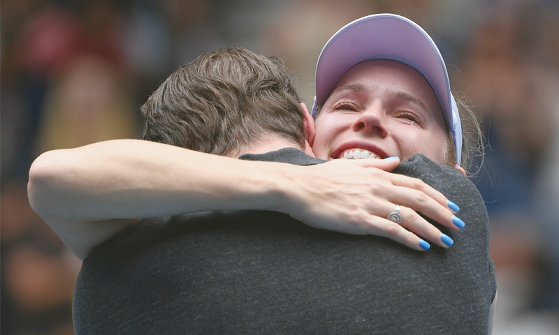 A TEARY-EYED Caroline Wozniacki hugs her husband following her loss to Ons Jabeur on Friday.—AP