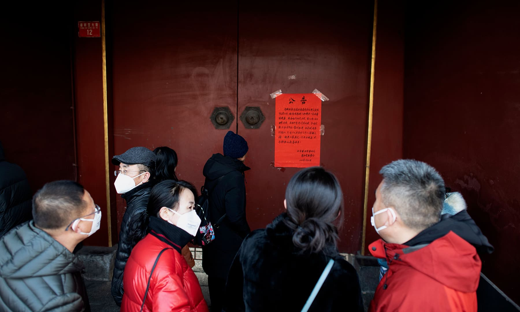 People wearing protective facemasks to help stop the spread of a deadly SARS-like virus which originated in the central city of Wuhan, stand in front of the closed gate of the Lama Temple in Beijing on January 25, 2020. — AFP