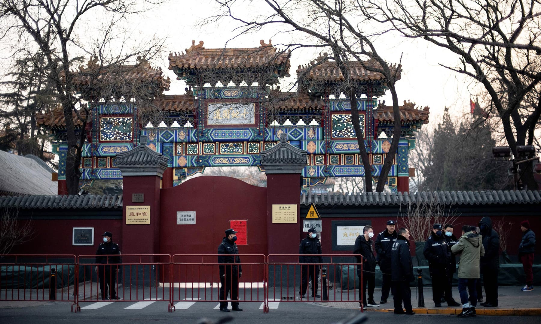 Policemen wearing protective facemasks to help stop the spread of a deadly SARS-like virus which originated in the central city of Wuhan, are seen in front of the closed gate of the Lama Temple in Beijing on January 25, 2020. — AFP