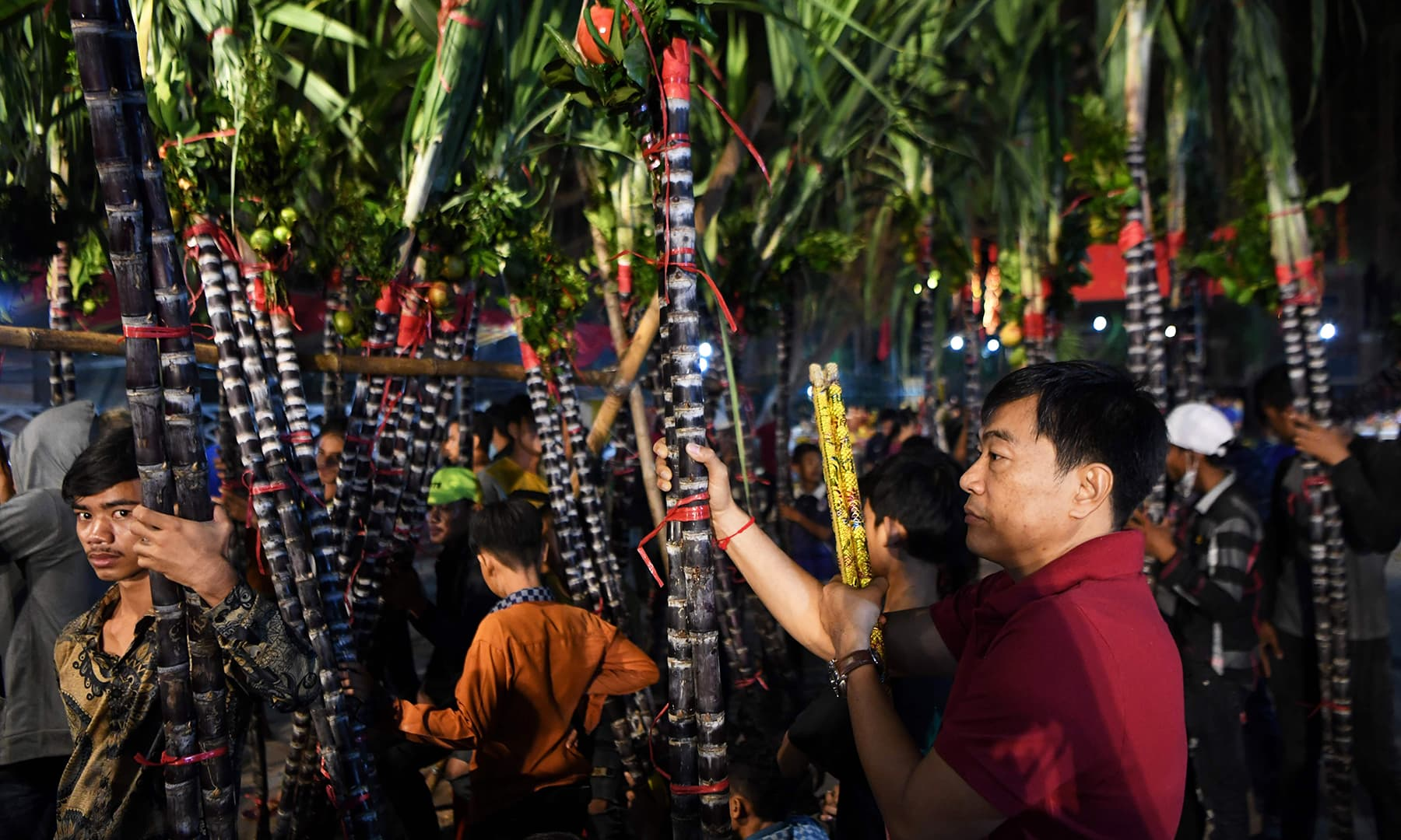 People hold sugar canes as they pray during the Lunar New Year at a temple in Kandal Province, Cambodia on January 25, 2020. — AFP