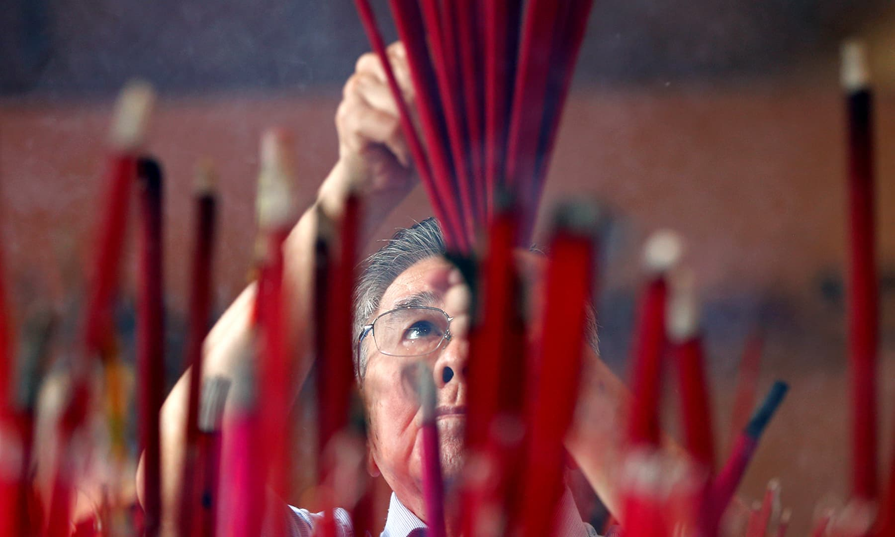A man prays during Chinese Lunar New Year celebrations at a temple in Jakarta, Indonesia on January 25, 2020. — Reuters
