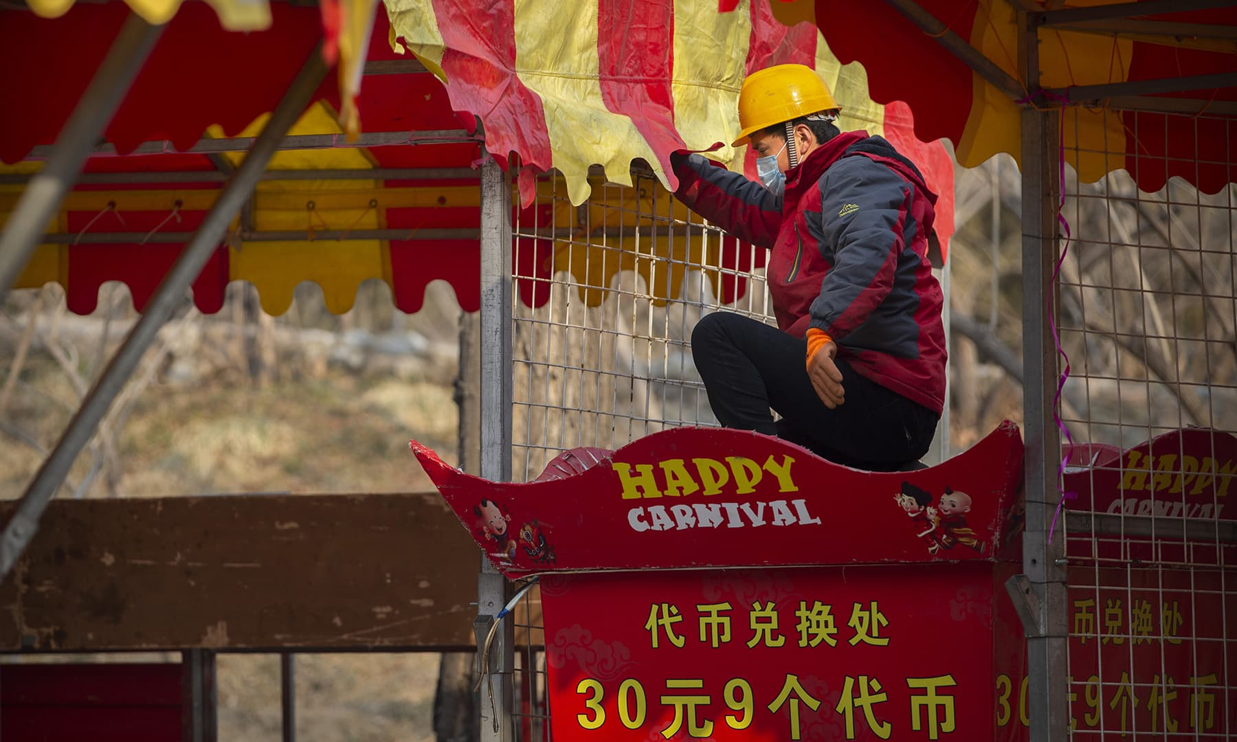 A worker dismantles a carnival built for a canceled Lunar New Year temple fair at Longtan Park in Beijing on January 25, 2020. — AP