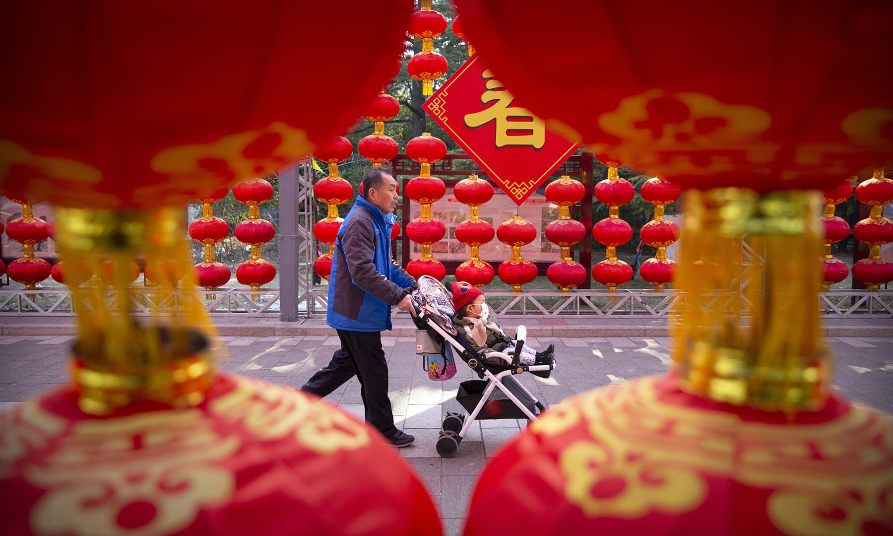 A man pushes a child in a stroller wearing a face mask past decorations for a cancelled Lunar New Year temple fair at Longtan Park in Beijing on January 25, 2020. — AP