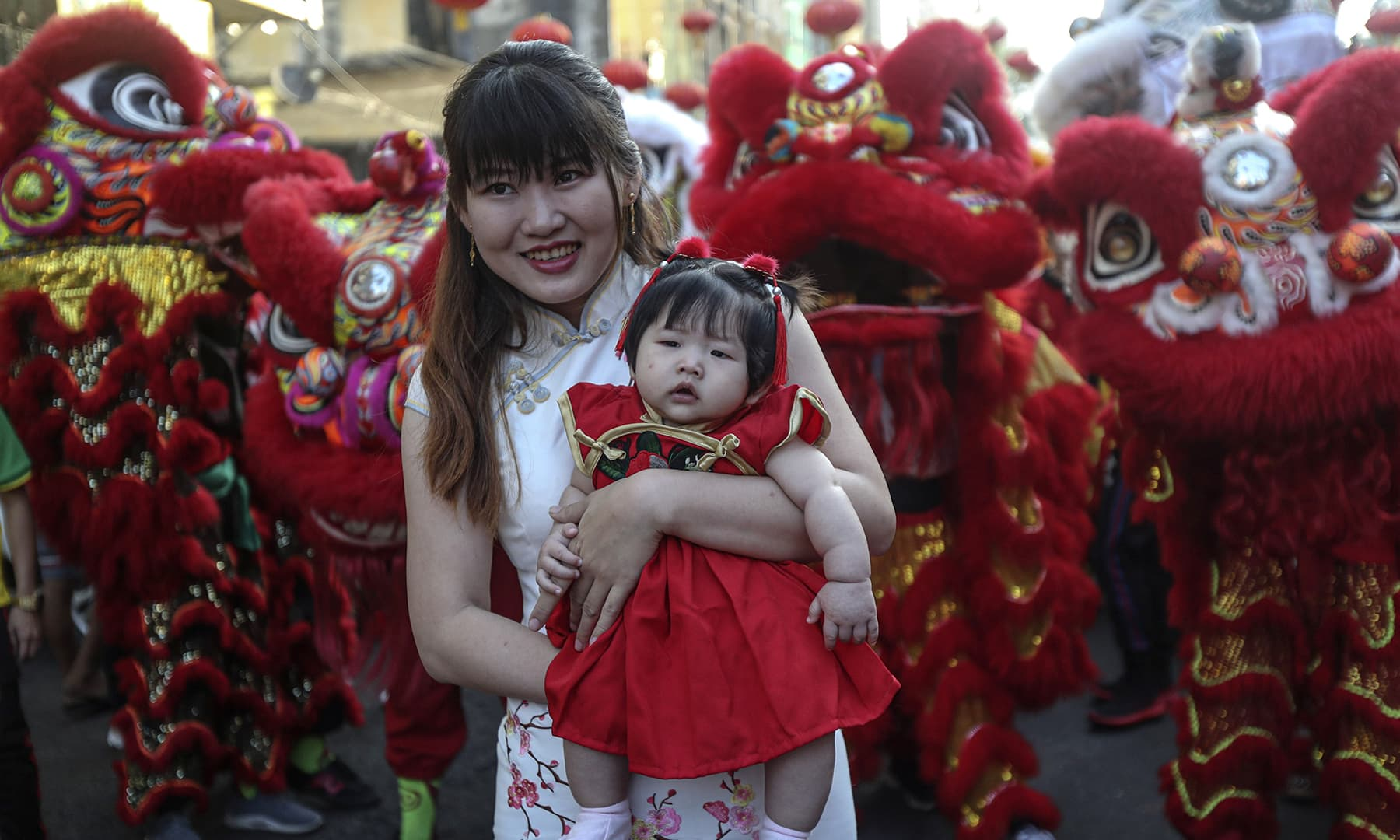 Local Chinese people pose for a photo in front of a lion dance troupe during a celebration to mark the Lunar New Year at Chinatown on January 25, 2020, in Yangon, Myanmar. — AP