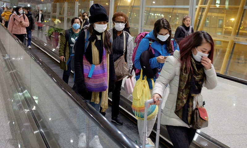 People wear face masks as they arrive at Beijing Capital International Airport in Beijing on January 25, 2020. —  Reuters