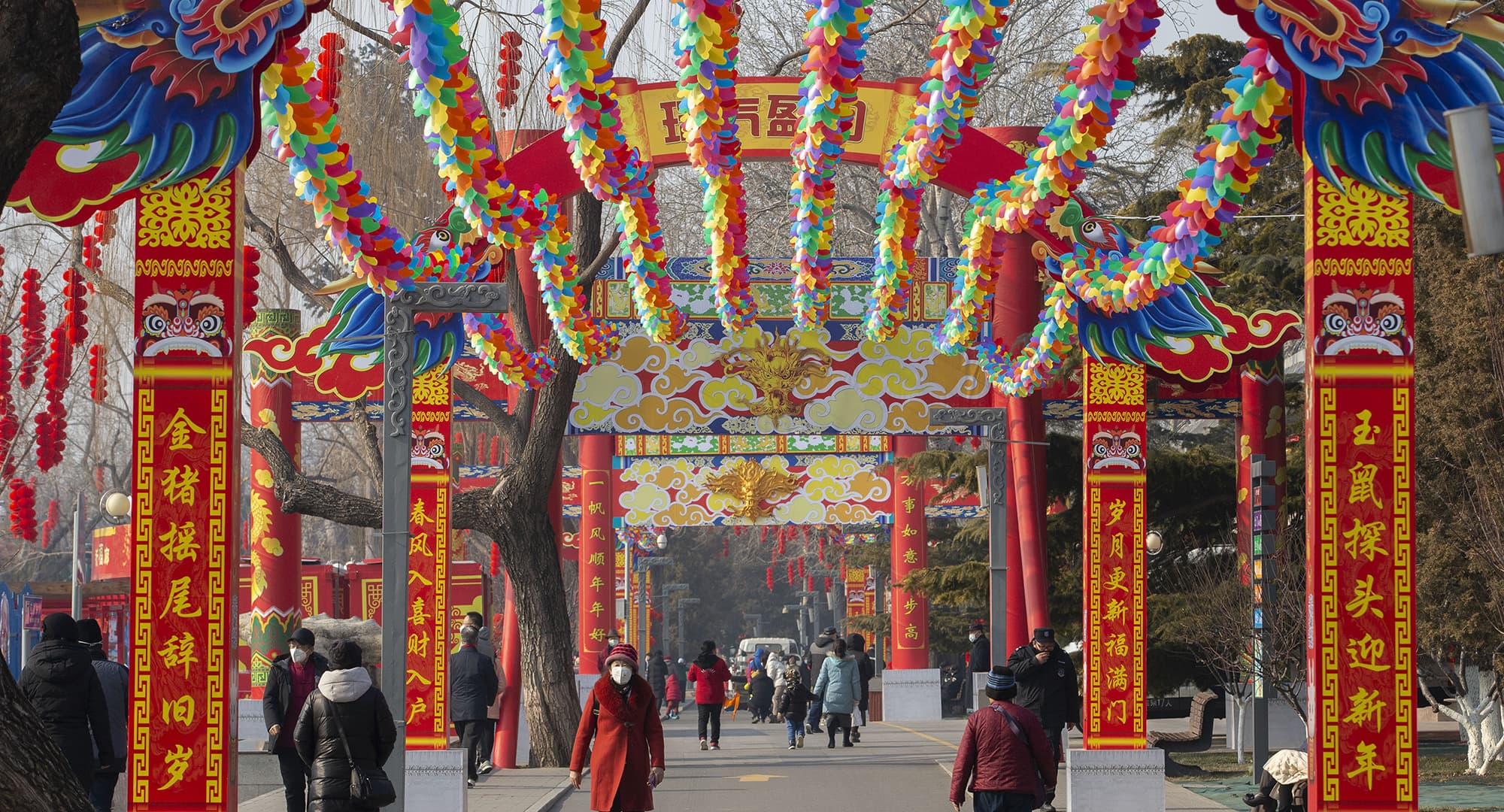 People wearing face masks walk under a canopy decorated with spinning colored fans for a canceled Lunar New Year temple fair at Longtan Park in Beijing, Saturday, Jan. 25, 2020. China's most festive holiday began in the shadow of a worrying new virus Saturday as the death toll surpassed 40, an unprecedented lockdown kept 36 million people from traveling and authorities canceled a host of Lunar New Year events. (AP Photo/Mark Schiefelbein) — Copyright 2020 The Associated Press. All rights reserved