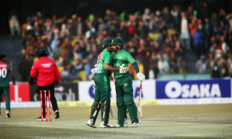 Skipper Babar Azam and Mohammad Hafeez walk over to congratulate each other at the 100-run mark of their 131-run partnership. — PCB