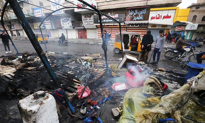 Iraqi anti-government demonstrators check burnt tents at a protest sit-in in Tahrir Square in the centre of the Iraqi capital Baghdad on Saturday. — AFP