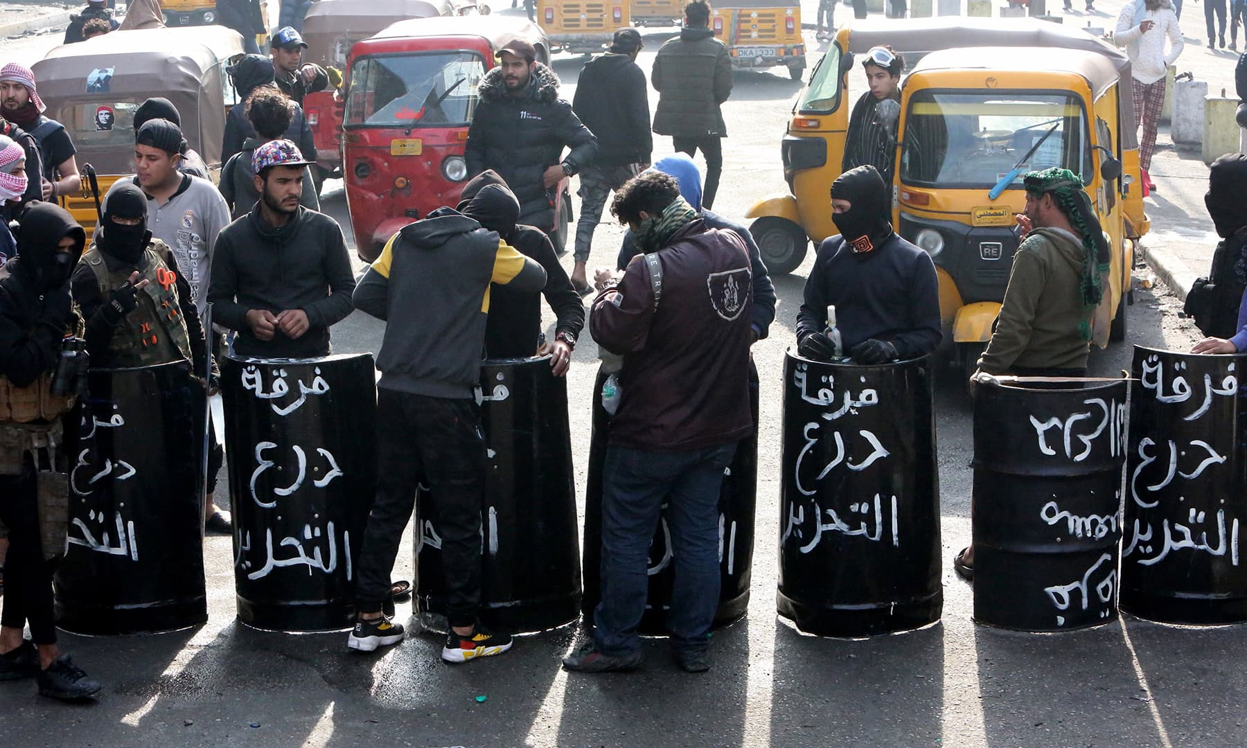 """Iraqi anti-government protesters carry black shields made out of metal drums, on which they had painted the words """"Tahrir Shield Squad."""", as they gather at al-Sinek bridge in the capital Baghdad on Saturday. — AFP"""