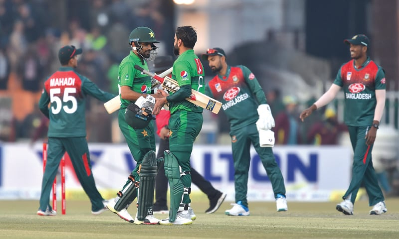 LAHORE: Pakistan captain Babar Azam and veteran player Mohammad Hafeez greet each other after leading their side to a thumping nine-wicket win in the second T20 as Bangladesh players look on.—M Arif/White Star
