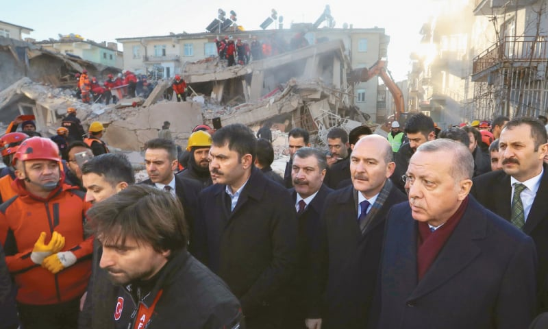 THIS handout picture shows President Recep Tayyip Erdogan looking on as rescue workers clear debris of a collapsed building in Elazig city, Turkey, on Saturday.—AFP