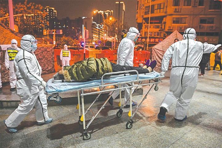 WUHAN (China): Medical personnel arrive with a patient at the Wuhan Red Cross Hospital on Saturday.—AFP
