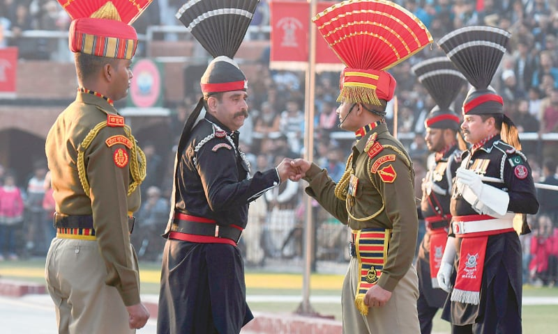 Indian Border Security Force personnel (dressed in brown) and Pakistan Rangers (dressed in black) take part in a Beating Retreat ceremony on India's republic day at the Wagah border on Sunday.—AFP