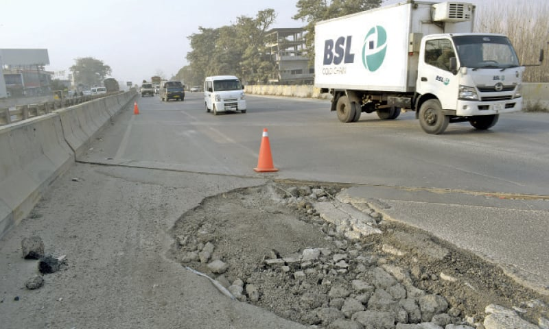 Potholes on the G.T. Road at the Wah Garden Bridge inconvenience commuters. — Dawn