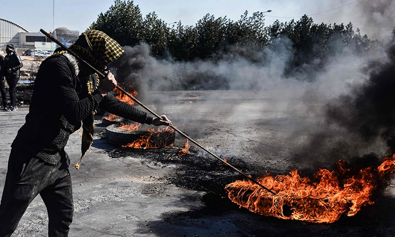 An anti-government protester stokes the flames of burning tyres at a make-shift roadblock along the road leading to Najaf International Airport in the central Iraqi holy shrine city on January 26, 2020. — AFP