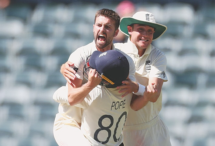 JOHANNESBURG: England paceman Mark Wood celebrates with team-mates Stuart Broad and Ollie Pope after dismissing South Africa's Rassie van der Dussen during the fourth Test at the Wanderers on Monday. —Reuters
