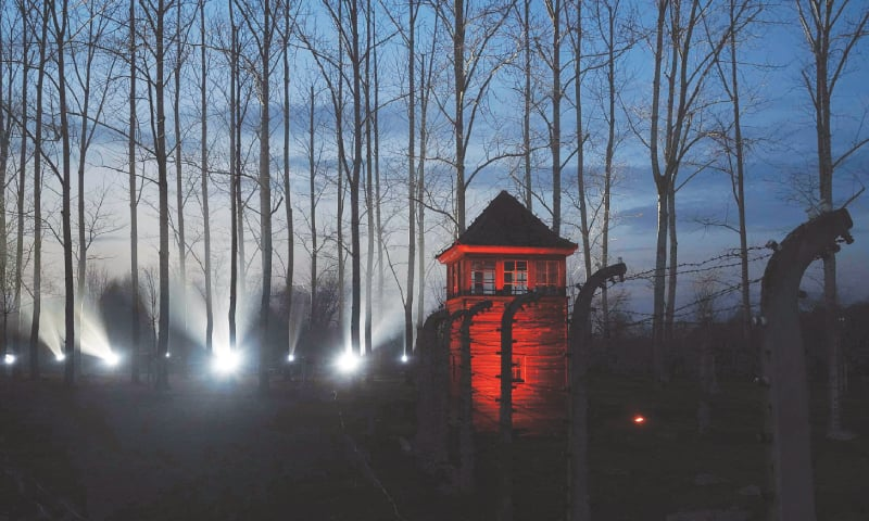 Oswiecim (Poland): An illuminated watch tower near the barbed wire fence enclosing the memorial site of the Auschwitz camp during ceremonies to commemorate the 75th anniversary of its liberation.—AFP