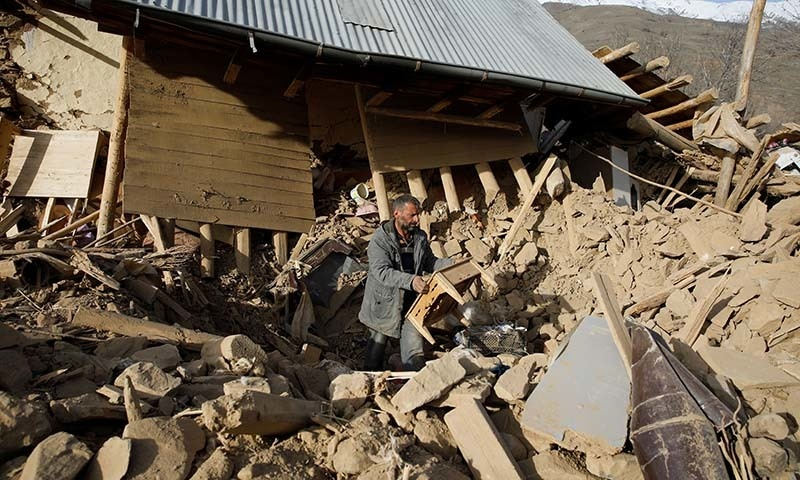A man clears debris outside a damage house, after an earthquake in Cevrimtas, Turkey,  on January 27. — Reuters