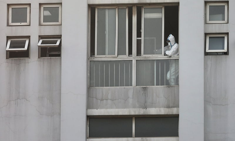 In this file photo, a medical staff member is seen by a window at the Jinyintan hospital, where the patients with pneumonia caused by the new strain of coronavirus are being treated, in Wuhan. — Reuters