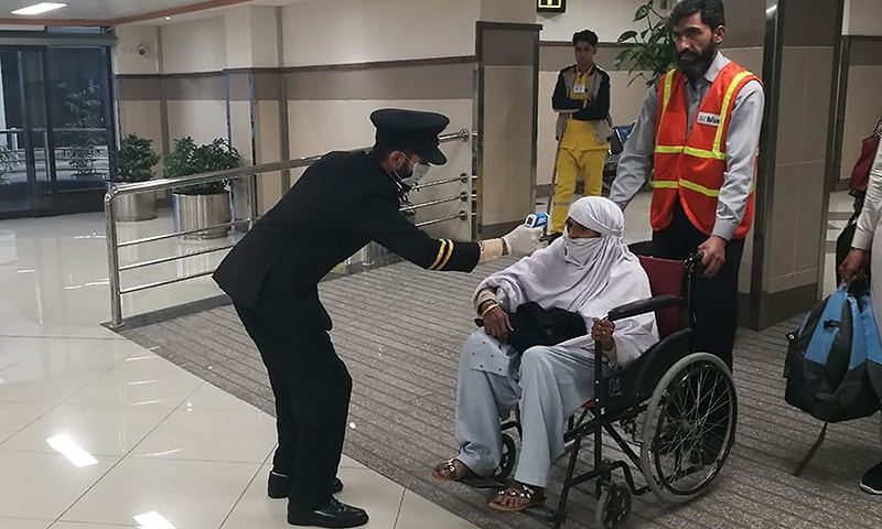 An airport official checks the temperature of a passenger upon his arrival at the Bacha Khan International Airport in Peshawar on January 27. — AFP