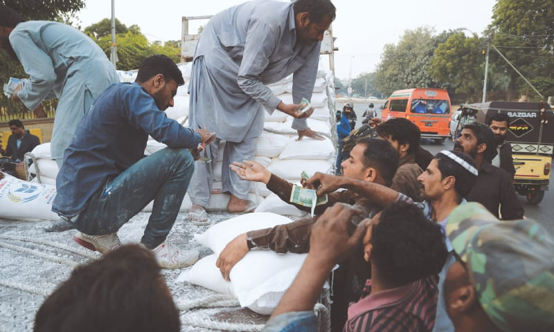 People buy flour at subsidised rates outside the Sindh Assembly building in this file photo.—White Star