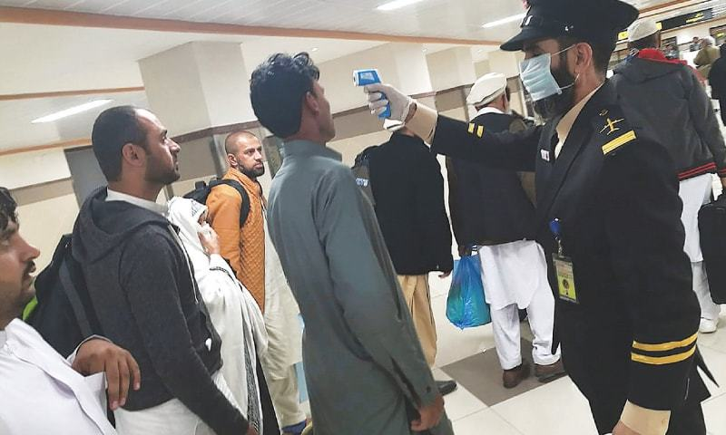An airport official checks the temperature of a passenger upon his arrival at the Bacha Khan International Airport on Monday.—AFP/File