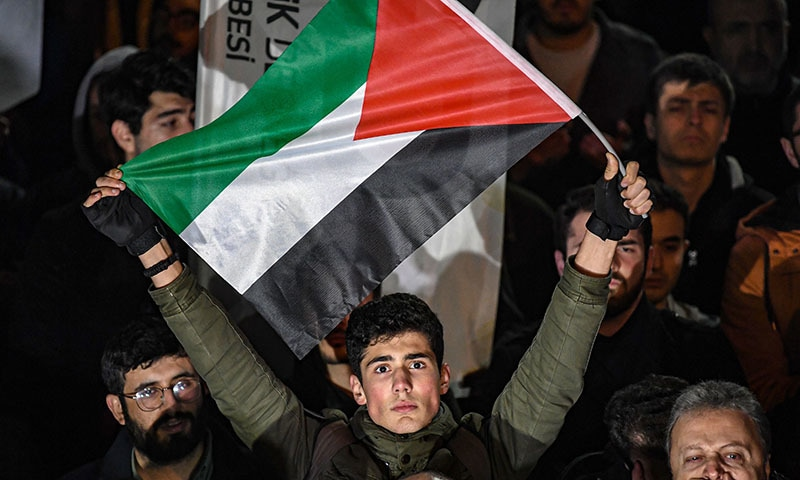 A man holds a flag of Palestine as protesters take part in a demonstration in front of the US consulate in Istanbul on January 29 to protest against the US peace plan. — AFP