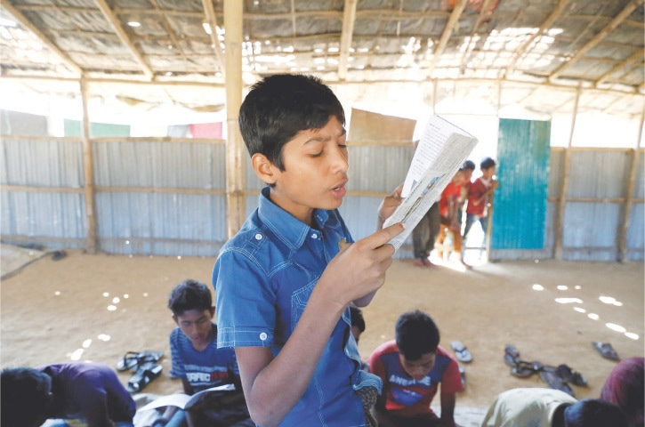 A child reads a book in a makeshift school run by Rohingya teachers in Kutupalong refugee camp  in Cox's Bazaar.—Reuters