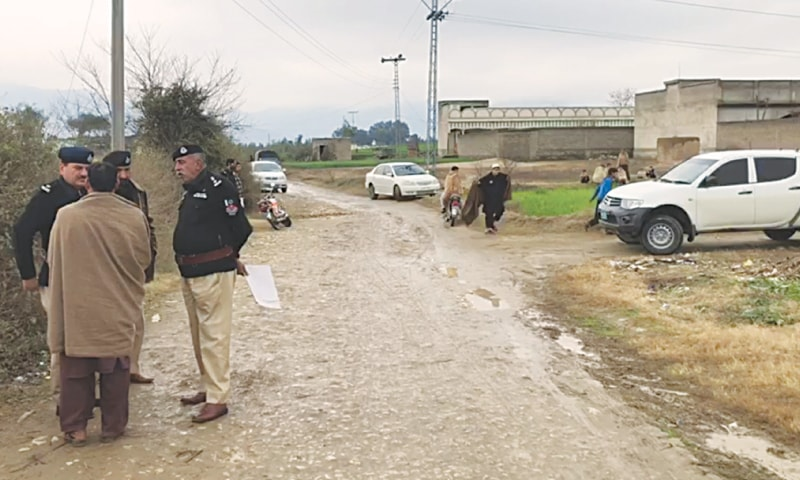 POLICE inspecting the area where two lady health workers were shot dead on Wednesday.—Dawn