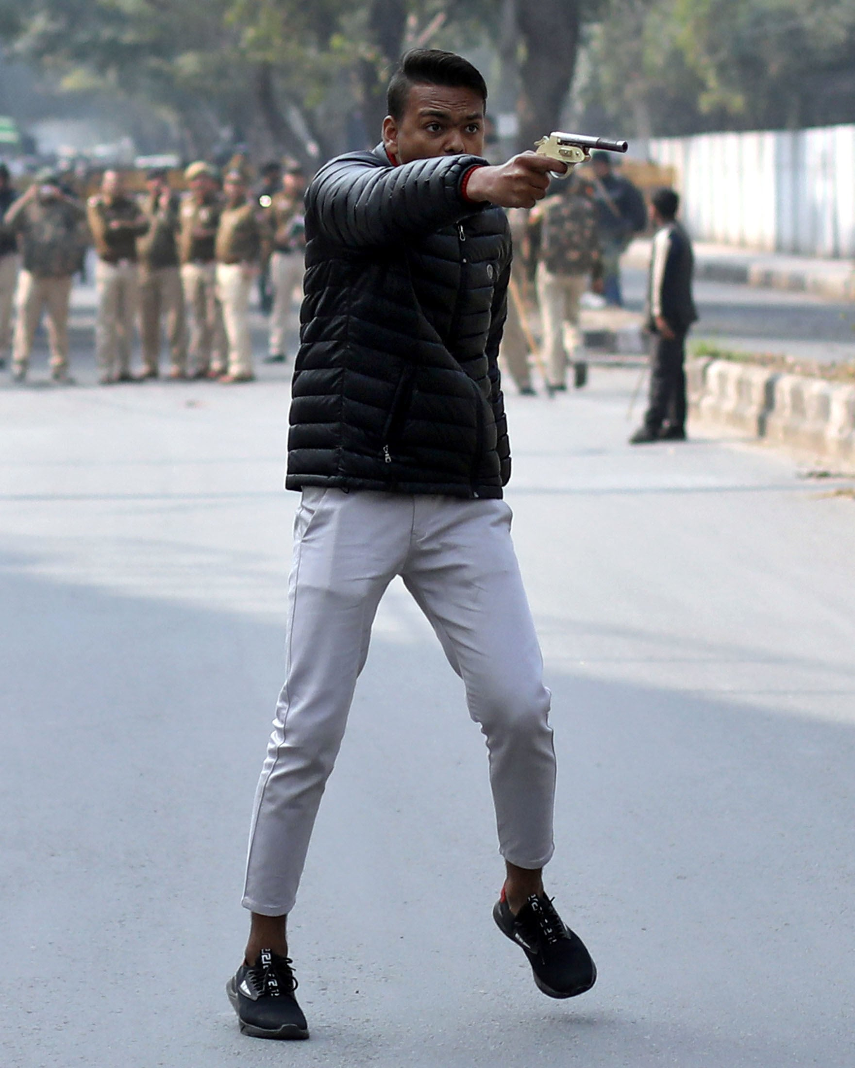 An unidentified man brandishes a gun during a protest against a new citizenship law outside the Jamia Millia Islamia university in New Delhi, India, on January 30. — Reuters