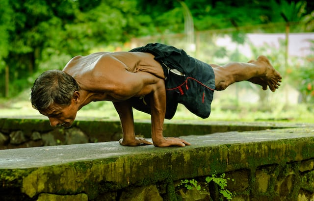 An unidentified old man does yoga in India,  demonstrating that age is just a number when it comes to fitness and good health