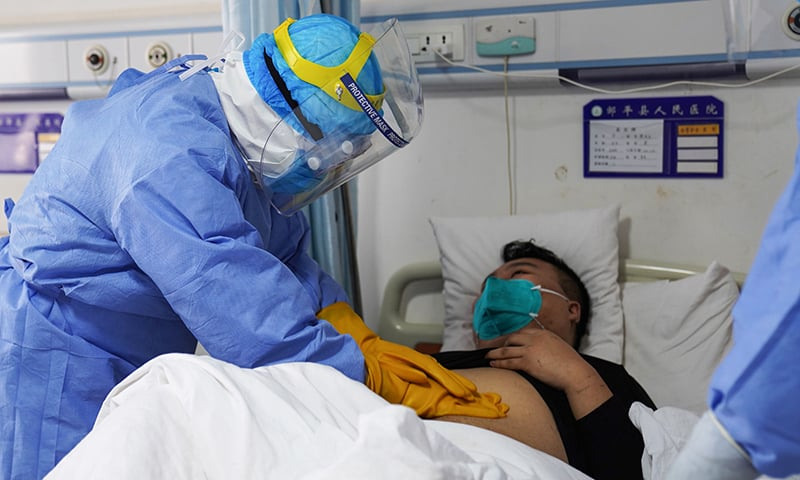 A medical staff member checks a patient infected by coronavirus inside an isolation ward at a hospital in Zouping in China's eastern Shandong province. — AFP