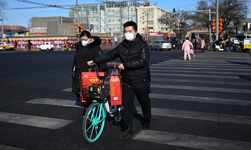 A man, wearing a mask, pushes a sharing bicycle with goods crossing a street in Beijing on February 1. — AFP