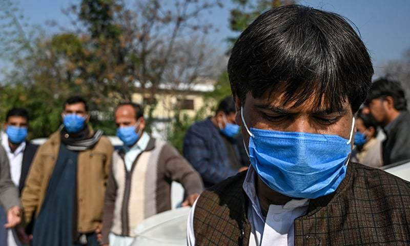 Drivers who work for a Pakistan-based Chinese company look on as they wear protective facemasks before their temperature's check in Islamabad on January 30, after instructions from Pakistani authorities to take preventive measures against the coronavirus. — AFP/File