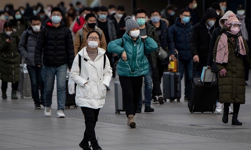 Passengers wearing facemasks arrive from different provinces at the Beijing Railway Station on February 1. — AFP