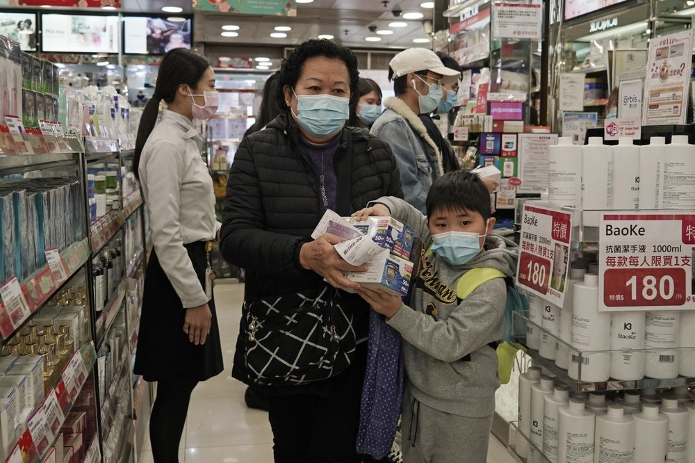 A woman and a boy purchase face masks in Hong Kong on Feb 1. ─ AP