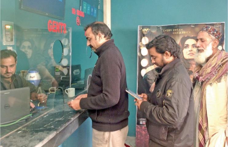 CINE-GOERS buy tickets at the cinema in Peshawar. — Dawn