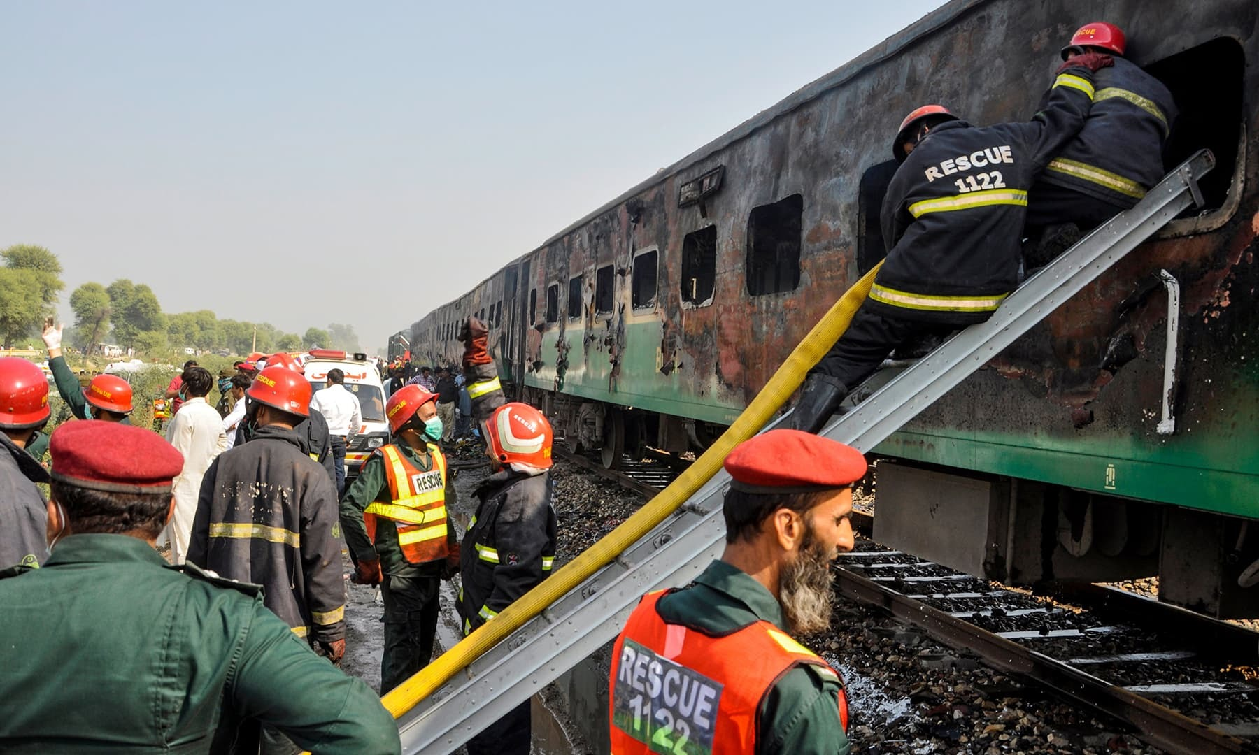 In this file photo, firefighters work to cool down the burnt-out train carriages after a passenger train caught on fire near Rahim Yar Khan on October 31, 2019. — AFP
