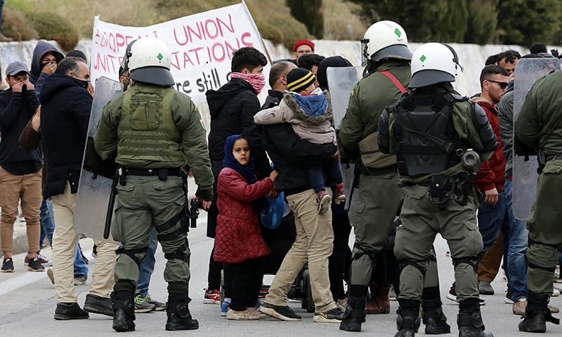 Riot police block a road to prevent protesting migrants from reaching the island's main town of Mytilene during a demonstration on the northeastern Aegean island of Lesbos, Greece, on Monday, Feb 3. — AP