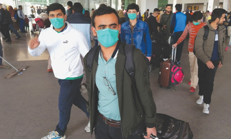 PAKISTANI students come out of Islamabad International Airport after returning from China on Monday.—AFP