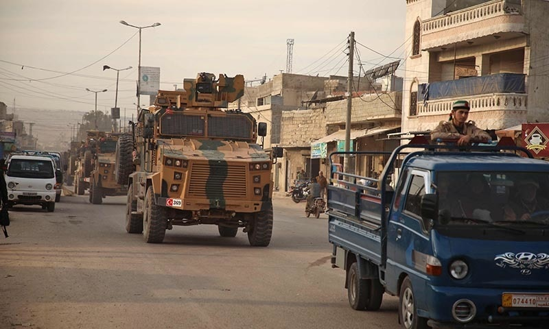 Turkish military vehicles drive in a convoy headed for the south of Idlib province as they pass by the town of Atareb in the western countryside of Aleppo on February 3. — AFP