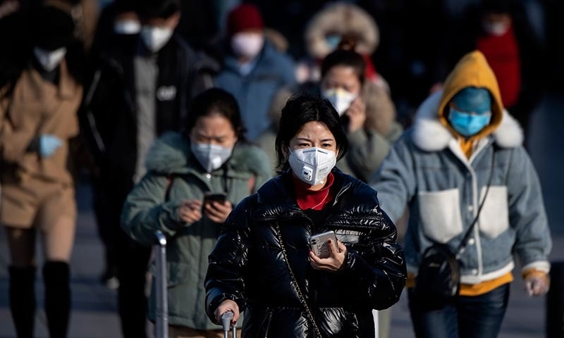 Travellers wearing facemasks arrive from various provinces at the Beijing Railway Station on February 3. — AFP