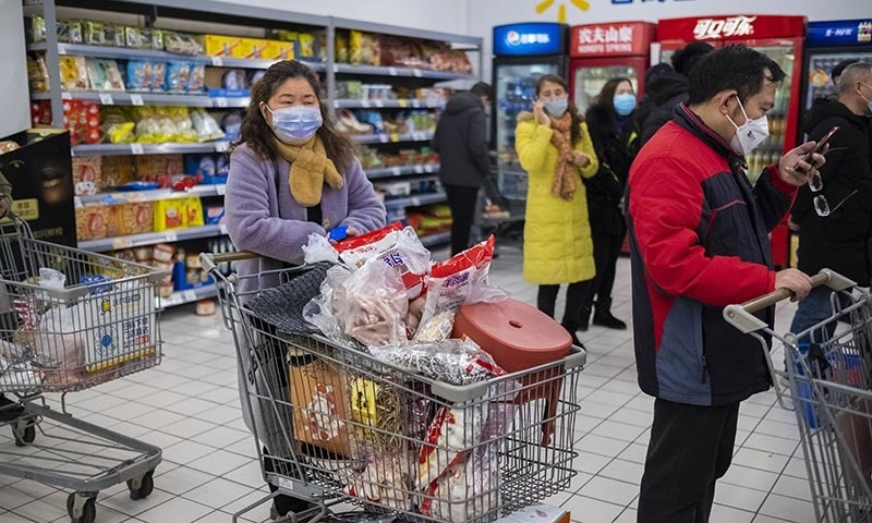 In this January 22, file photo, shoppers wear face masks as they line up at a grocery store in Wuhan in central China's Hubei Province. — AP