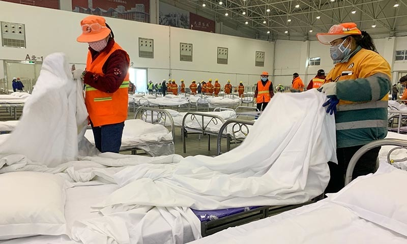 Workers set up beds at an exhibition centre that was converted into a hospital in Wuhan in China's central Hubei province on February 4. — AFP
