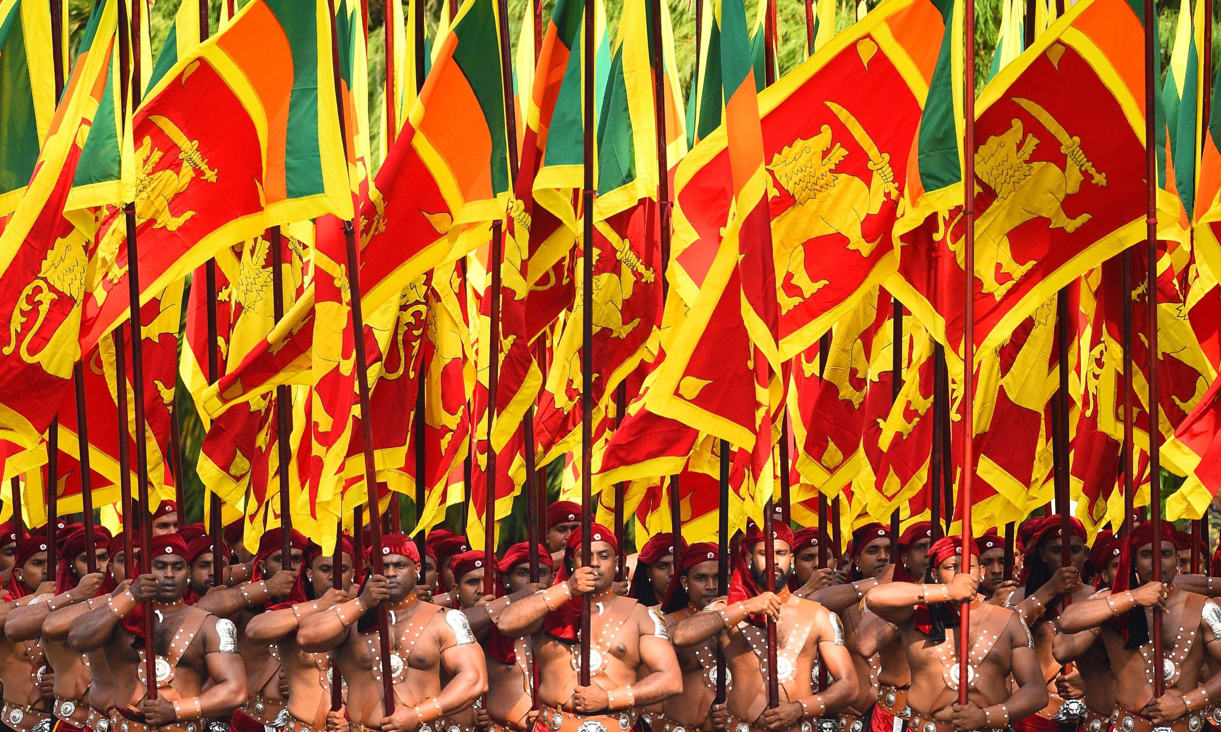 Sri Lankan military personnel march in their traditional dress holding national flags during the country's 72nd Independence Day celebrations in Colombo on Feb 4. — AFP