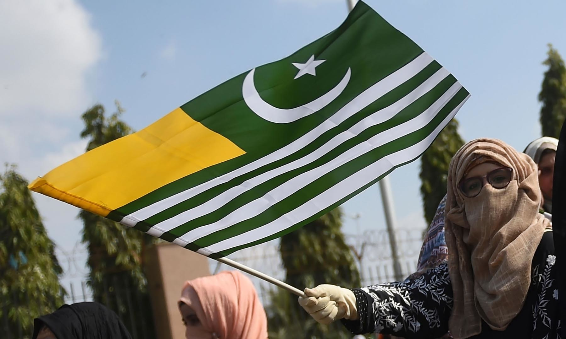 A protester waves Kashmiri flag in Karachi during a demonstration against India February 4. — AFP