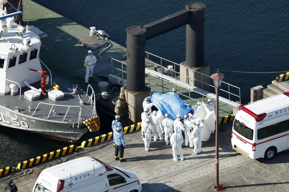 Medical workers in protective suits lead a passenger who tested positive for a new coronavirus from the cruise ship Diamond Princess at Yokohama Port in Yokohama, south of Tokyo, on Wednesday. ─ AP