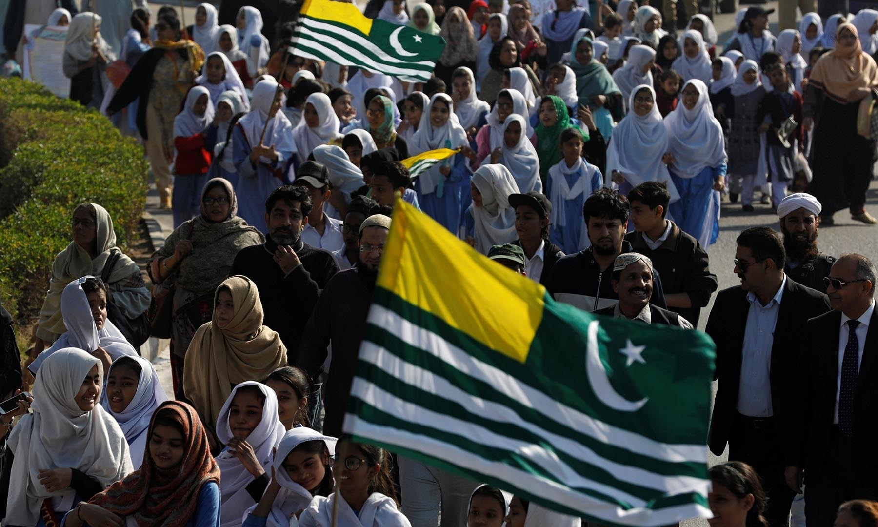 Students and teachers carry flags as they attend a march to mark Kashmir Solidarity Day at the mausoleum of the Mohammad Ali Jinnah in Karachi. — Reuters