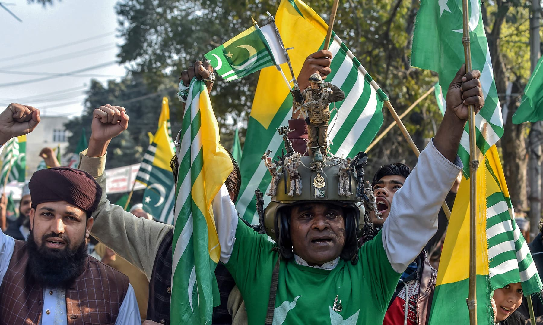 Protesters hold flags as they shout slogans during a demonstration to mark Kashmir Solidarity Day in Lahore. — AFP